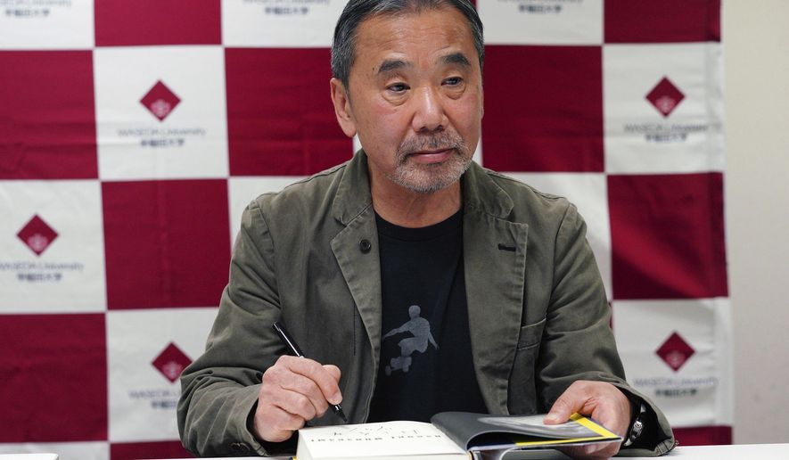 "FILE - In this Nov. 3, 2018, file photo, Japanese novelist Haruki Murakami signs his autograph on his novel ""Killing Commendatore"" during a press conference at Waseda University in Tokyo. The acclaimed Japanese novelist Murakami, hosting a special radio show from home, painted a brighter side of the world with his favorite music, and said Friday, May 22, 2020, the fight against the coronavirus is a challenge to human wisdom in figuring out ways to help and care each other. (AP Photo/Eugene Hoshiko, File)"