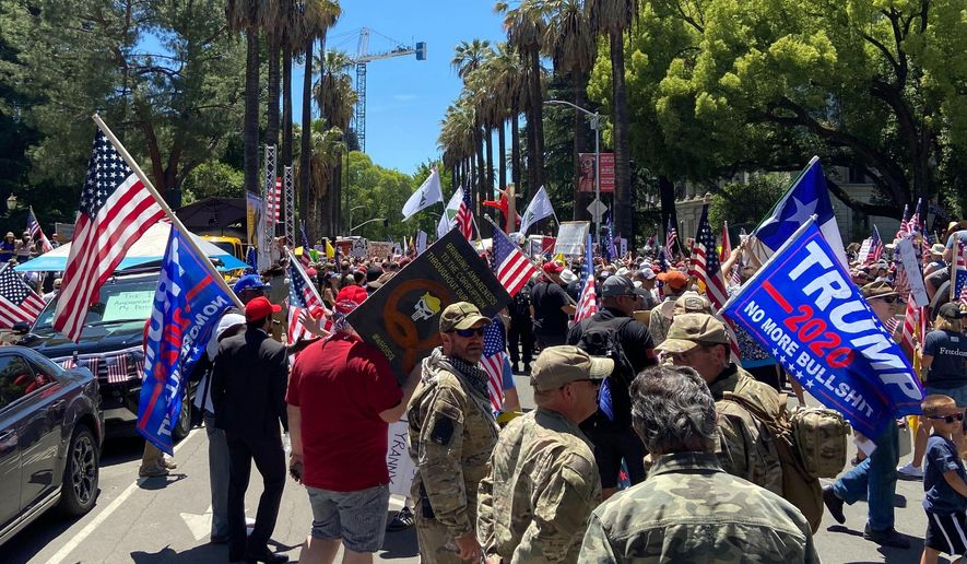 """Protesters gathered outside the """"Liberty Fest"""" rally in front of California State Capitol, Saturday, May 23, 2020, in Sacramento, Calif., to protest Gov. Gavin Newsom's Stay At Home Order to stem the coronavirus outbreak. (AP Photo/Cuneyt Dil)"""