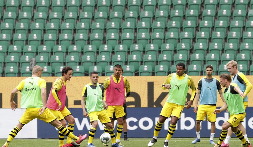 Dortmund players kick a ball during warmup before the German Bundesliga soccer match between VfL Wolfsburg and Borussia Dortmund in Wolfsburg, Germany, Saturday, May 23, 2020. The German Bundesliga is the world's first major soccer league to resume after a two-month suspension because of the coronavirus pandemic. (AP Photo/Michael Sohn, Pool)