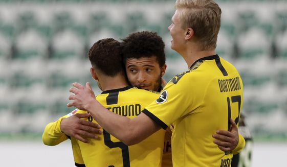 Dortmund's Achraf Hakimi, left, celebrates with Jadon Sancho and Erling Haaland, right, after scoring his side's second goal during the German Bundesliga soccer match between VfL Wolfsburg and Borussia Dortmund in Wolfsburg, Germany, Saturday, May 23, 2020. The German Bundesliga is the world's first major soccer league to resume after a two-month suspension because of the coronavirus pandemic. (AP Photo/Michael Sohn, Pool)