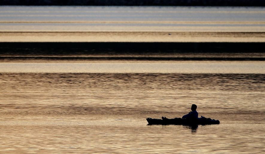 A man floats on Shawnee Mission Lake at dusk Friday, May 22, 2020, in Lenexa, Kan. As coronavirus-related stay-at-home orders are lifted, people are flocking to lakes, parks and other nearby attractions to celebrate the long Memorial Day weekend. (AP Photo/Charlie Riedel)