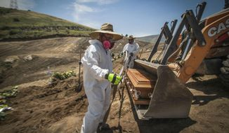 In this May 5, 2020 photo, workers in full protection gear as a precaution against the new coronavirus, unload a coffin that contain the remains of a person who died from the new coronavirus, in an area of the municipal cemetery set apart for victims of COVID-19, in Tijuana, Mexico. Citing a threat of the virus from Mexico, the Trump administration has banned hundreds of thousands of people from crossing the southern border with emergency measures that prohibit nonessential traffic and reject asylum seekers without a hearing. (AP Photo/Joebeth Terriquez)