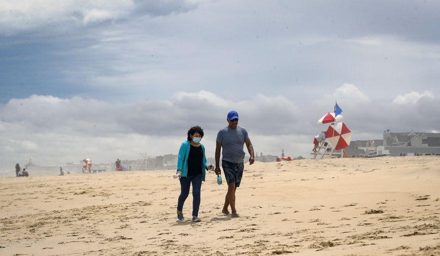 People walk on a mostly empty beach Saturday, May 23, 2020, in Belmar, N.J., during the coronavirus pandemic. (AP Photo/John Minchillo)