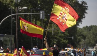 People wave Spanish flags during a drive-in protest organised by Spain's far-right party Vox against the Spanish government's handling of the nation's coronavirus outbreak in Madrid, Spain Saturday, May 23, 2020. (AP Photo/Manu Fernandez)