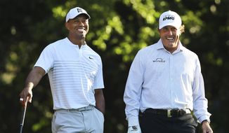 """In this April 3, 2018, file photo, Tiger Woods, left, and Phil Mickelson share a laugh on the 11th tee box while playing a practice round for the Masters golf tournament at Augusta National Golf Club in Augusta, Ga. The next match involving Tiger Woods and Phil Mickelson involves a $10 million donation for COVID-19 relief efforts, along with plenty of bragging rights in a star-powered foursome May 24 at Medalist Golf Club. Turner Sports announced more details Thursday, May 7, 2020, for """"The Match: Champions for Charity,"""" a televised match between Woods and Peyton Manning against Mickelson and Tom Brady. (Curtis Compton/Atlanta Journal-Constitution via AP, File)  **FILE**"""