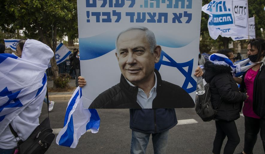 """Supporters of Israel's Prime Minister Benjamin Netanyahu hold banners and wave Israeli flags outside his residence in Jerusalem, Sunday, May 24, 2020. Israeli Prime Minister Benjamin Netanyahu was heading to court to face corruption charges in the first criminal trial ever against a sitting Israeli leader. The Hebrew writing say """" Netanyahu. you will never walk alone"""". (AP Photo/Ariel Schalit)"""