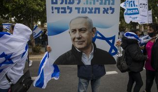 "Supporters of Israel's Prime Minister Benjamin Netanyahu hold banners and wave Israeli flags outside his residence in Jerusalem, Sunday, May 24, 2020. Israeli Prime Minister Benjamin Netanyahu was heading to court to face corruption charges in the first criminal trial ever against a sitting Israeli leader. The Hebrew writing say "" Netanyahu. you will never walk alone"". (AP Photo/Ariel Schalit)"