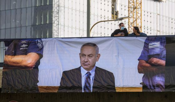 A poster depicts Israel's Prime Minister Benjamin Netanyahu superimposed in a court defendant's dock, in Tel Aviv, Israel, Sunday, May 24, 2020. His long-awaited criminal trial begins Sunday in Jerusalem. (AP Photo/Oded Balilty)