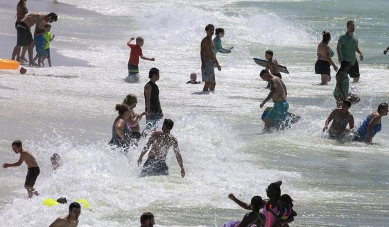 People enjoy Pensacola Beach in Pensacola, Fla., Saturday, May 23, 2020, during the coronavirus pandemic. (David Grunfeld/The Advocate via AP)