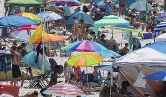 People visit Pensacola Beach in Pensacola, Fla., Saturday, May 23, 2020, during the coronavirus pandemic. (David Grunfeld/The Advocate via AP)