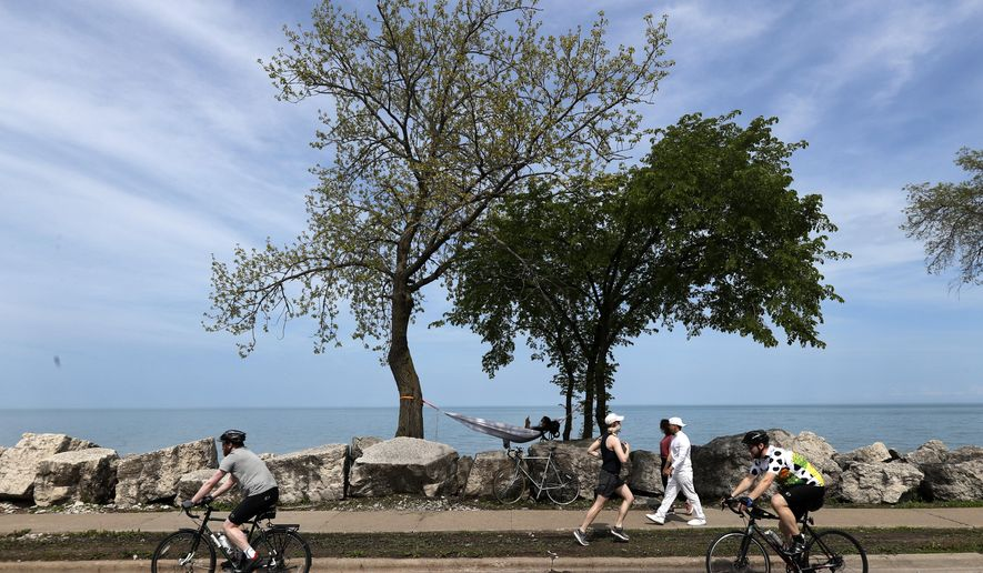Miles Suggs from Minneapolis, Minn., and a student at DePaul University in Chicago, relaxes in a hammock along the Lake Michigan shore as others pass by Sunday, May 24, 2020, in Evanston, Ill. (AP Photo/Charles Rex Arbogast)