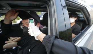 A man in a car receives a body temperature check as he arrives to watch the Stage X drive-in concert at KINTEX parking lot in Goyang, South Korea, Saturday, May 23, 2020. The concert's aims is to provide entertainment for South Korean citizens who have been craving for music events that have been suspended during the coronavirus outbreak. (AP Photo/Ahn Young-joo)