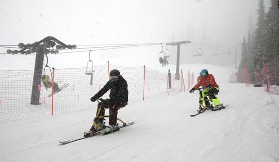 FILE - In this April 10, 2019, file photo, riders on ski-bikes participating in the 30th Annual Enduro, a fundraiser and ski-a-thon to benefit a local cause, heads towards base of Pallavicini Chair at Arapahoe Basin Ski Area, Colo. The ski resort will open for limited spring skiing and riding on Wednesday, May 27, 2020. This follows approval of Summit County's request for a variance from the state public health order by the Colorado Department of Public Health and Environment. At this time, closing day is still to be determined. (Hugh Carey/Summit Daily News via AP, File)