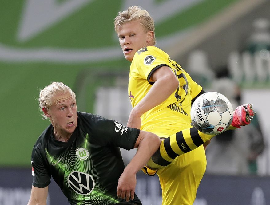 Wolfsburg's Xaver Schlager, left, vies for the ball with Dortmund's Erling Haaland during the German Bundesliga soccer match between VfL Wolfsburg and Borussia Dortmund in Wolfsburg, Germany, Saturday, May 23, 2020. The German Bundesliga is the world's first major soccer league to resume after a two-month suspension because of the coronavirus pandemic. (AP Photo/Michael Sohn, Pool)