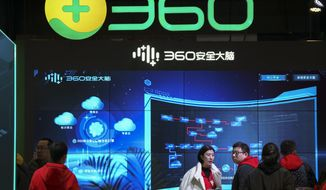 """In this photo released by Xinhua News Agency, visitors tour the Chinese internet security firm Qihoo 360 showcasing it 5G digital security and protection system at the World 5G Convention in Beijing on Nov. 21, 2019. One of China's biggest tech companies has criticized the Trump administration for """"politicizing business"""" after it slapped export sanctions on 33 more Chinese enterprises and government entities. (Li Xin/Xinhua via AP)"""