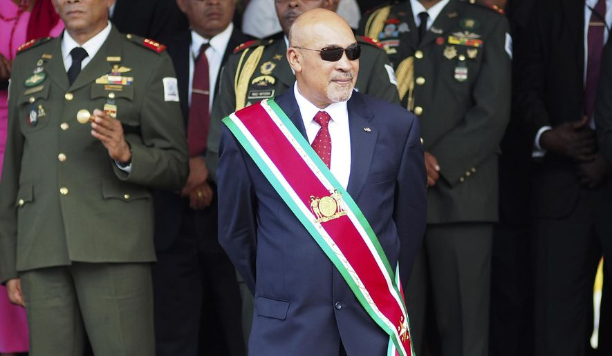 """FILE - In this Aug. 12, 2015 file photo, Suriname President Desire """"Desi"""" Delano Bouterse observes a military parade, after being sworn in for his second term, in Paramaribo, Suriname. The president stands a fair chance of holding onto power as the small South American nation elects a new National Assembly on Monday, May 25, 2020, a body that will choose the next president in August. (AP Photo/Ertugrul Kilic, File)"""