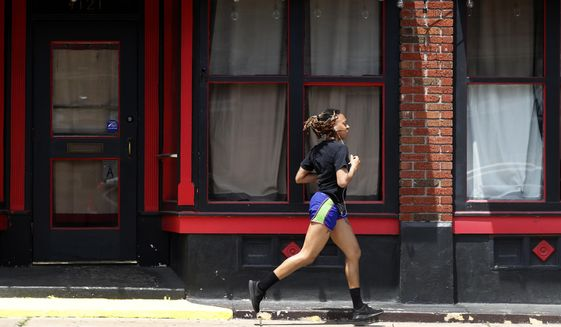 In this Thursday, May 7, 2020, file photo, a person jogs past a closed nightclub in St. Louis. Running is seeing an increase in participation since the coronavirus outbreak began taking off in the United States. (AP Photo/Jeff Roberson, File)  **FILE**