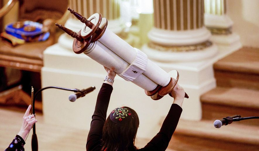 In this Feb. 1, 2020, file photo, Rabbi Jacqueline Mates-Muchin holds a Torah scroll aloft during Shabbat morning service at Temple Sinai in Oakland, Calif. (AP Photo/Noah Berger, File)  **FILE**