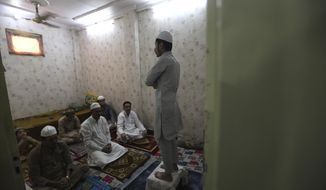 Indian Muslims gather for Eid al-Fitr prayers inside their house in New Delhi, India, Monday, May 25, 2020. The holiday of Eid al-Fitr, the end of the fasting month of Ramadan, a usually joyous three-day celebration has been significantly toned down as coronavirus cases soar. (AP Photo/Manish Swarup)