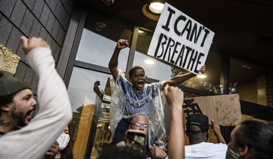 People gather at a police precinct during a protest for George Floyd in Minneapolis on Tuesday, May 26, 2020. Four Minneapolis officers involved in the arrest of the black man who died in police custody were fired Tuesday, hours after a bystander's video showed an officer kneeling on the handcuffed man's neck, even after he pleaded that he could not breathe and stopped moving. (Richard Tsong-Taatarii/Star Tribune via AP)