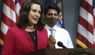 FILE - In this Thursday, May 21, 2020 file photo provided by the Michigan Office of the Governor, Michigan Gov. Gretchen Whitmer speaks during a news conference in Lansing, Mich. The owner of a boat service company said the husband of Michigan's governor dropped her name while pleading to get his boat in the water for Memorial Day weekend. (Michigan Office of the Governor via AP, Pool, File)