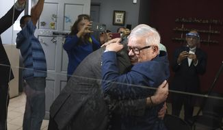 Gay equality activist Marco Castillo, right, embraces his longtime partner Rodrigo Campos, after they were married before a judge, in San Jose, Costa Rica, Tuesday, May 26, 2020. Costa Rica became the latest country to legalize same-sex marriage early Tuesday when a ruling from its supreme court went into effect ending the country's ban. (AP Photo/Carlos Gonzalez)