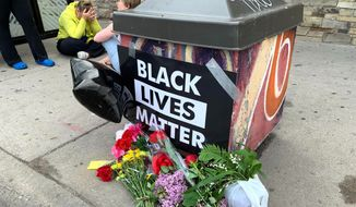 People gather around a makeshift memorial Tuesday, May 26, 2020, in Minneapolis, near where an black man was taken into police custody the day before who later died. The FBI and Minnesota agents are investigating the death of a black man in Minneapolis police custody after video from a bystander showed a white officer kneeling on his neck during his arrest as he pleaded that he couldn't breathe.  (AP Photo/Jeff Baenen)