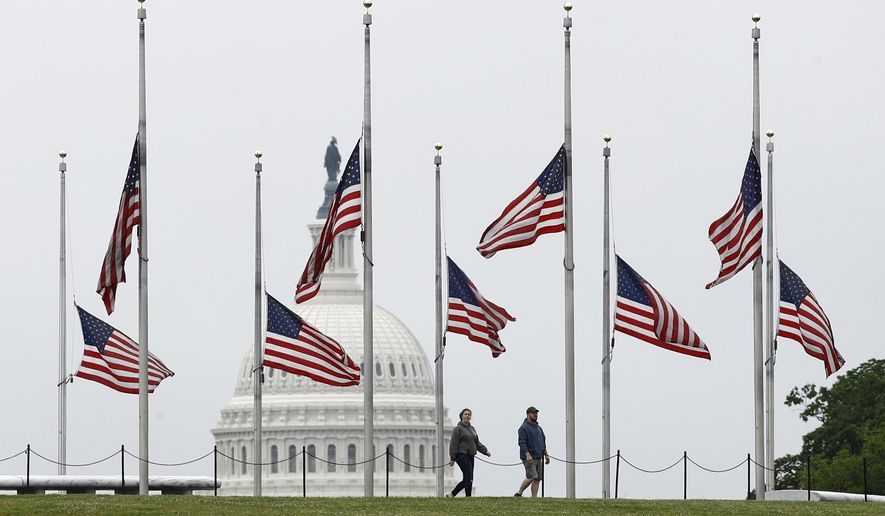 In this May 22, 2020 file photo, people walk past American flags flying at half-staff at the Washington Monument in Washington.  (AP Photo/Patrick Semansky)  **FILE**