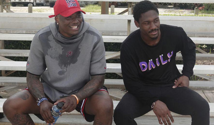 Washington Redskins quarterback Dwayne Haskins, left, sits with the Buffalo Bills wide receiver Stefon Diggs, Wednesday, May 27, 2020, at Holiday Park in Fort Lauderdale, Fla. (Joe Cavaretta/South Florida Sun-Sentinel via AP)