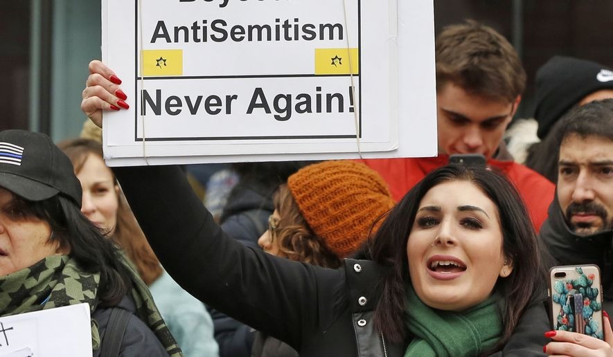 In this Jan. 19, 2019, file photo, political activist Laura Loomer holds uo a sign across the street from a rally organized by Women's March NYC after she barged onto the stage interrupting Women's March NYC director Agunda Okeyo who was speaking during a rally in New York. (AP Photo/Kathy Willens, File)