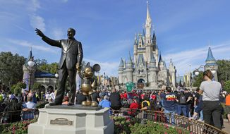 In this Jan. 9, 2019 photo, guests watch a show near a statue of Walt Disney and Micky Mouse in front of the Cinderella Castle at the Magic Kingdom at Walt Disney World in Lake Buena Vista, part of the Orlando area in Fla. Officials from SeaWorld and Disney World say they hope to open their theme parks in Orlando, Fla., in June and July. A city task force approved the plans on Wednesday, May 27, 2020. (AP Photo/John Raoux, File)  **FILE**