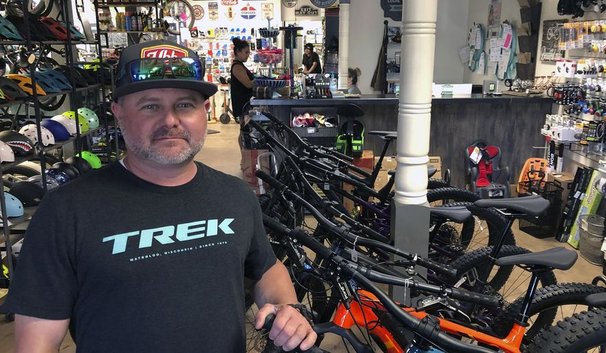 Brian Morris, owner of Freeride Bike Company in Gilbert, Ariz., poses in the store Friday, May 22, 2020. Morris faced a difficult scenario when the coronavirus pandemic started leading to shutdowns across the nation. If Arizona Gov. Doug Ducey opted to include bike shops among the businesses deemed nonessential, Freeride Bike Company, which he owns with his wife Ashleigh, would have to shutter its doors for who knows how long. When Ducey deemed bike shops essential, it turned out to be huge boon for their business as cooped-up Americans sought ways to go outside and get moving. (AP Photo/John Marshall)