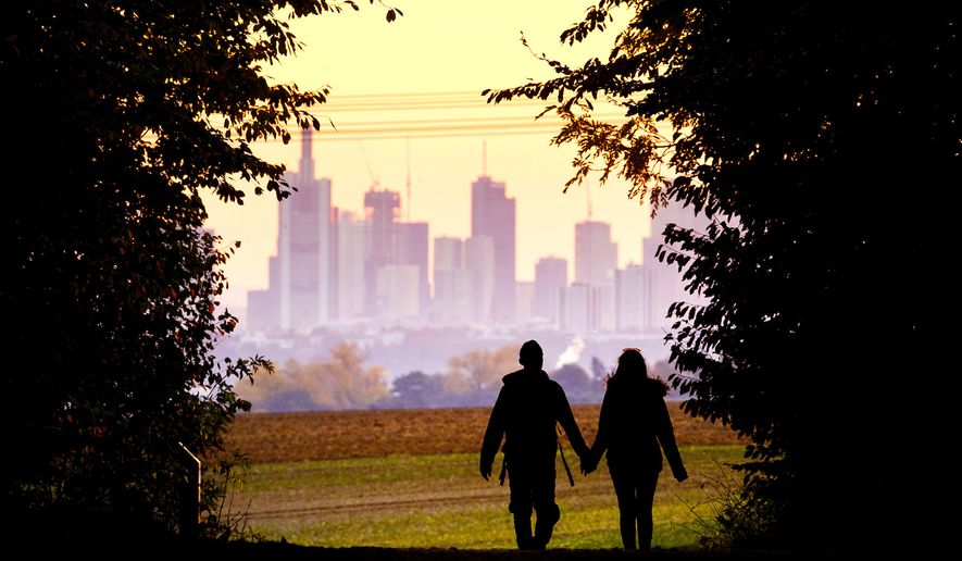 A young couple walks through a forest with the Frankfurt skyline in the background near Frankfurt, Germany, on Oct. 21, 2018. (Associated Press) **FILE**