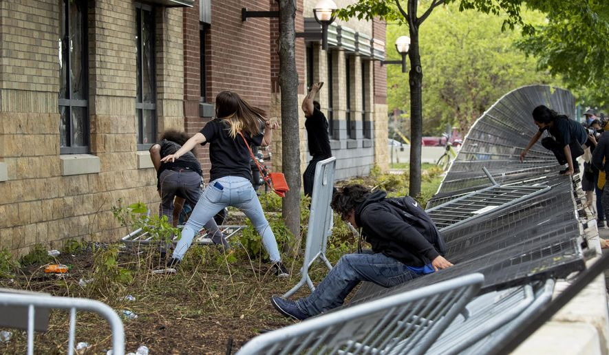 Protesters damage properties at the Minneapolis 3rd Police Precinct in Minneapolis on Wednesday, May 27, 2020. The mayor of Minneapolis called Wednesday for criminal charges against the white police officer seen on video kneeling against the neck of a handcuffed black man who complained that he could not breathe and died in police custody. (Carlos Gonzalez/Star Tribune via AP)