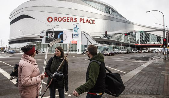 In this March 12, 2020, file photo, people talk outside Rogers Place, the home ice of the Edmonton Oilers, in Edmonton, Alberta. Rogers Place is one of the possible locations the NHL has zeroed in on to host playoff games if it can return amid the coronavirus pandemic. The league will ultimately decide on two or three locations for games, with government regulations, testing and COVID-19 frequency among the factors for the decision that should be coming within the next three to four weeks.(Jason Franson/The Canadian Press via AP) ** FILE **