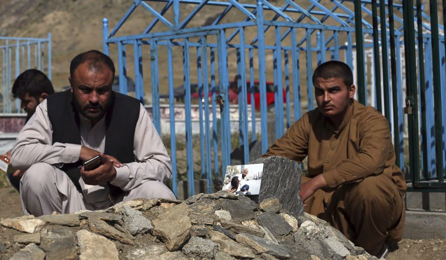In this Wednesday, May 20, 2020 photo, members of the Aryubi family mourn over the graves of Dr. Yousuf Aryubi, in photo, and two of his siblings who lost their lives to COVID-19, in Kabul, Afghanistan. Dr. Aryubi's family assumed they just had a bad cold, as one after another, they came down with fevers and coughs -- all because one of the Afghan capital's main hospitals never told them the results of his coronavirus test. Their tragedy points to how a broken-down health system, slow government response and public attitudes have left Afghanistan deeply vulnerable to the global pandemic. (AP Photo/Rahmat Gul)