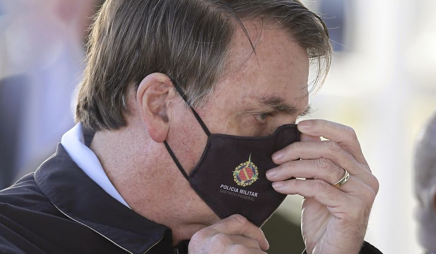 Brazil's President Jair Bolsonaro adjusts his face mask as he speaks to supporters while departing his official residence, Alvorada Palace, in Brasilia, Brazil, Thursday, May 21, 2020. (AP Photo/Eraldo Peres) ** FILE **