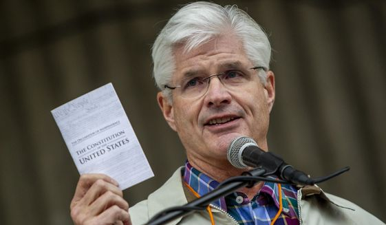 "FILE - In this Monday, May 18, 2020 file photo, Michigan Senate Majority Leader Mike Shirkey, R-Clark Lake, holds a copy of the Constitution while speaking during the ""American Patriot Rally-Sheriffs speak out"" event at Rosa Parks Circle in downtown Grand Rapids, Mich. Shirkey said Michigan Gov. Gretchen Whitmer lied and engaged in a cover-up by asking for the removal of a social media post about her husband's attempt to get his boat in the water during the coronavirus pandemic, only to later acknowledge he did drop her name as a joke. (Cory Morse/The Grand Rapids Press via AP, File)"