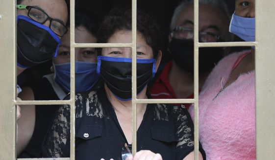 A family peers from the window of their home as they wait to receive boxes of free food, during a lockdown to curb the spread of the new coronavirus, in Bogota, Colombia, Monday, May 4, 2020. The U.N. World Food Program is warning that upward of at least 14 million people could go hungry in Latin America as the coronavirus pandemic rages on, shuttering people in their homes, drying up work and crippling the economy. (AP Photo/Fernando Vergara)