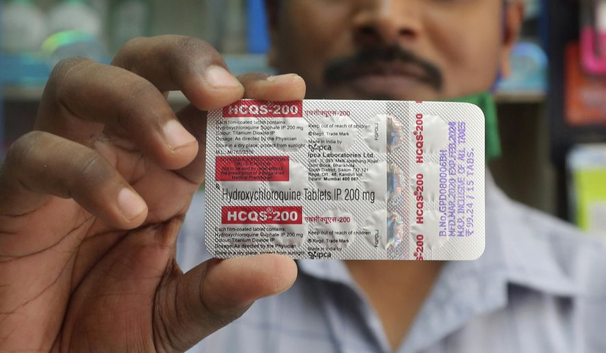 In this Tuesday, May 19, 2020, file photo, a chemist holds a pack of hydroxychloroquine tablets in Mumbai, India. (AP Photo/Rafiq Maqbool) ** FILE **