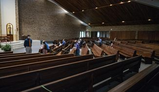 Parishioners attend a service presided by Father John Paul Erickson as pews were closed off to allow social distancing and a maximum capacity of 250 at Transfiguration Catholic Church in Oakdale, Minn., on Wednesday, May 27, 2020.  The church is one of the first Minnesota congregations to offer public worship since houses of worship shut down to prevent the spread of Covid 19. (Richard Tsong-Taatarii/Star Tribune via AP)