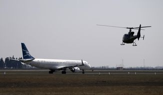 In this photo taken on Wednesday, March 15, 2017, a Montenegrin army helicopter flies near Montenegro Airlines Embraer E195LR sits on the tarmac at the Golubovci airport, near Podgorica, Montenegro.  Serbia's authorities Wednesday May 27, 2020, have banned Montenegro's national carrier from operating flights from Belgrade after the small Adriatic state excluded Serbian citizens from a list of countries with which it will reopen its borders after declaring an end to the coronavirus epidemic. (AP Photo/Darko Vojinovic)