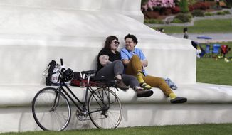 In this photo taken May 17, 2020, sweethearts Hannah Smith, left, of Vancouver, British Columbia, and Jabree Robinson, of Bellingham, Wash., sit on the base of the Peace Arch as they visit at the border between Canada and the U.S. at Peace Arch Park, in Blaine, Wash. With the border closed to nonessential travel amid the global pandemic, families and couples across the continent have found themselves cut off from loved ones on the other side. But the recent reopening of Peace Arch Park, which spans from Blaine into Surrey, British Columbia, at the far western end of the 3,987-mile contiguous border, has given at least a few separated parents, siblings, lovers and friends a rare chance for some better-than-Skype visits. (AP Photo/Elaine Thompson)