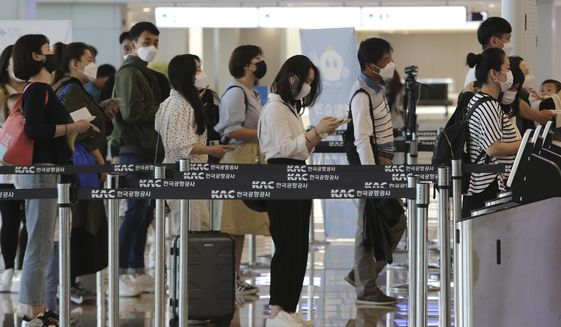 Passengers wearing face masks line up to board their planes at the domestic flight terminal of Gimpo airport in Seoul, South Korea, Wednesday, May 27, 2020. The quarantine authorities on Wednesday began to require all airplane passengers to wear masks amid the coronavirus pandemic. (AP Photo/Ahn Young-joon) ** FILE **