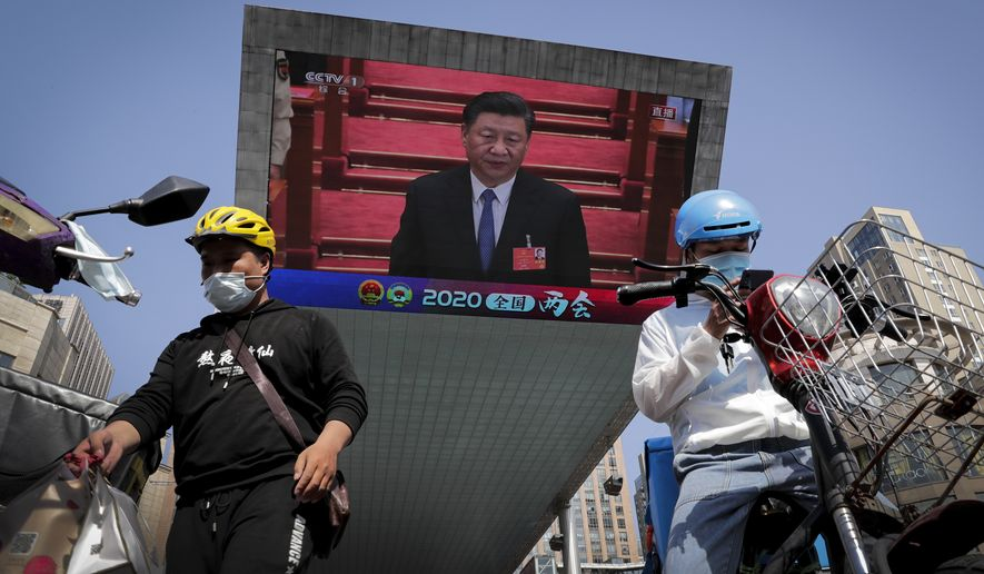 Food delivery workers wearing face masks to protect against the spread of the new coronavirus prepare to delivery foods near a TV screen showing Chinese President Xi Jinping attending the closing ceremony of the National People's Congress in a news report, in Beijing, China, Thursday, May 28, 2020. China's ceremonial legislature on Thursday endorsed a national security law for Hong Kong that has strained relations with the United States and Britain. (AP Photo/Andy Wong) **FILE**
