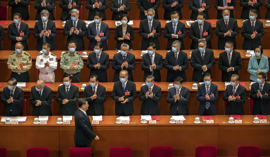 Delegates applaud as Chinese President Xi Jinping arrives for the closing session of China's National People's Congress (NPC) in Beijing, Thursday, May 28, 2020. China's ceremonial legislature has endorsed a national security law for Hong Kong that has strained relations with the United States and Britain. (AP Photo/Mark Schiefelbein)