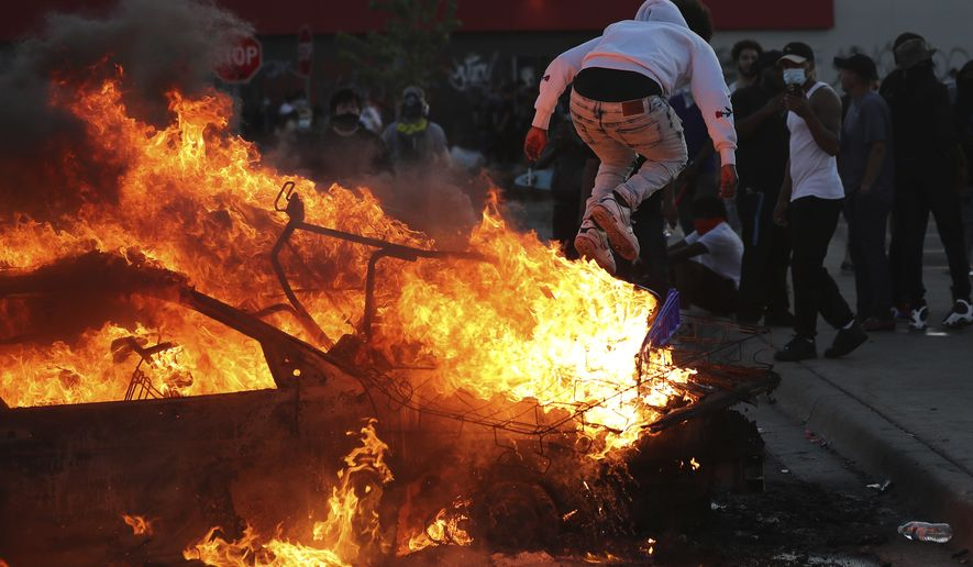 A man jumps off a burning car in a Target parking lot Thursday, May 29, 2020, in Minneapolis during a third night of unrest following the Monday death of George Floyd in Minneapolis police custody. (David Joles/Star Tribune via AP)