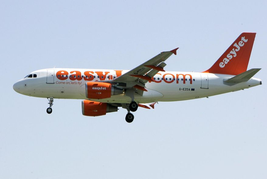 FILE - In this file photo dated Wednesday, April 23, 2008, an EasyJet jetliner lands at the Milan Linate airport, Italy. European budget airline eastJet said Thursday May 28, 2020, it plans to cut up to a third of its 15,000-strong workforce as the global aviation industry struggles to cope with the COVID-19 pandemic. (AP Photo/Antonio Calanni, FILE)