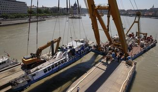 FILE - In this Tuesday, June 11, 2019, file photo, a crane lifts the sightseeing boat out of the Danube river in Budapest, Hungary. Preparations are underway for commemorations to be held on the first anniversary of the May 29, 2019, mishap on the Danube River in which a sightseeing boat carrying mostly tourists from South Korea sank after a collision with a river cruise ship.  Just seven of the 33 South Korean tourists aboard the Hableany (Mermaid) survived the nighttime collision at Budapest's Margit Bridge. (AP Photo/Darko Bandic, File)