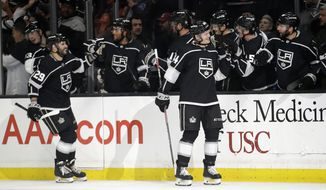 FILE - In this March 9, 2020, file photo, Los Angeles Kings' Mikey Anderson, right, celebrates his goal with teammates during the first period of an NHL hockey game against the Colorado Avalanche, in Los Angeles. The Los Angeles Kings were the NHL's hottest team before the coronavirus pandemic ended the regular season prematurely. They're hoping they can eventually build on that success whenever they get back on the ice. (AP Photo/Marcio Jose Sanchez, File)